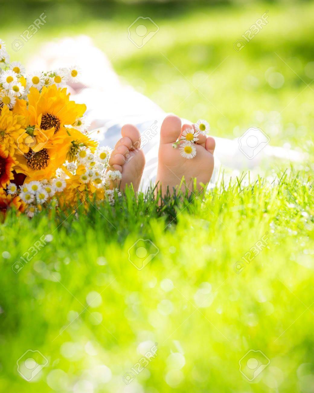 children`s feet with spring flower on green grass Stock Photo - 17347838