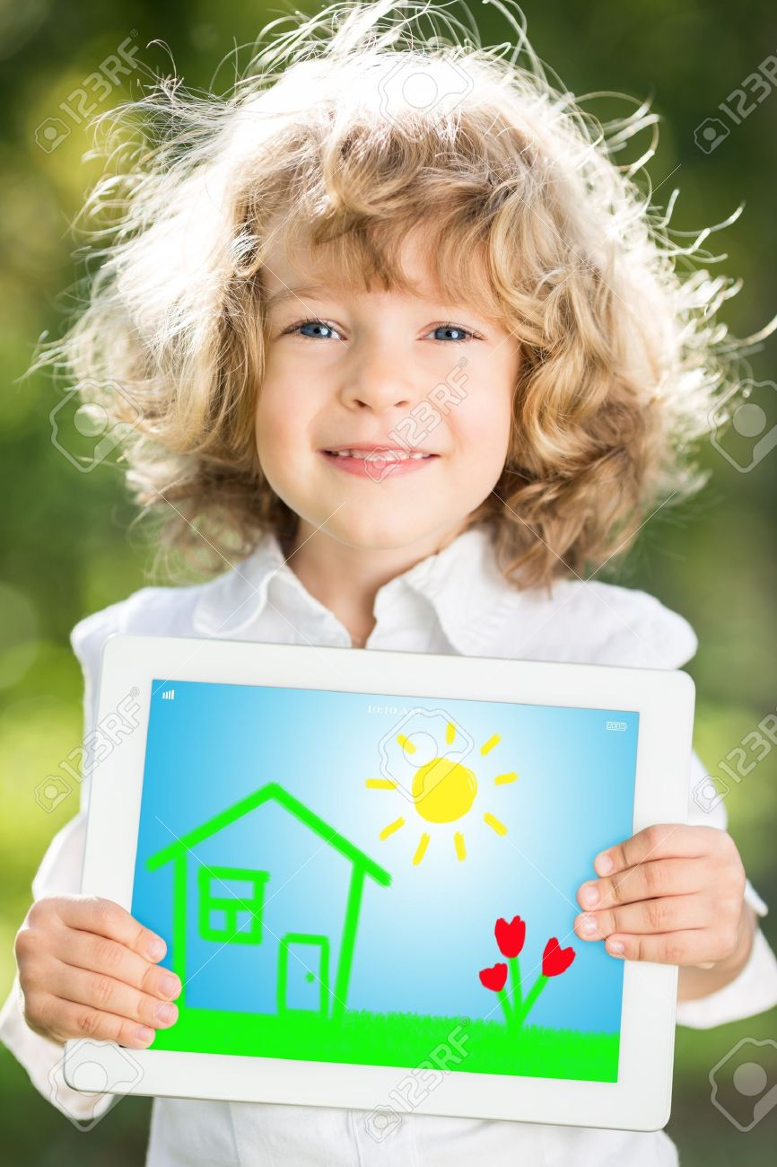 Happy smiling child holding tablet PC against green spring background Stock Photo - 17540998