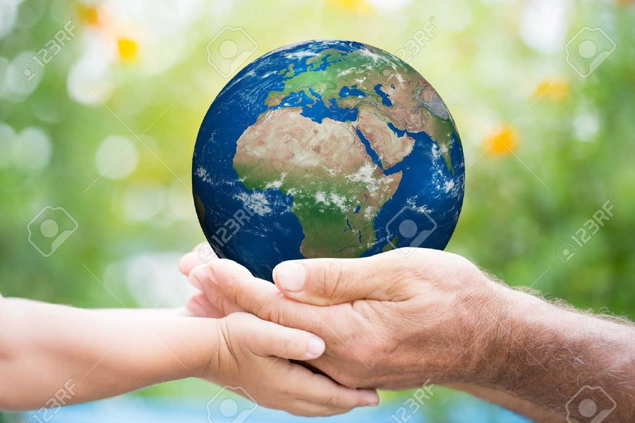 Child and senior man holding planet Earth in hands against green spring background. Stock Photo - 17546591
