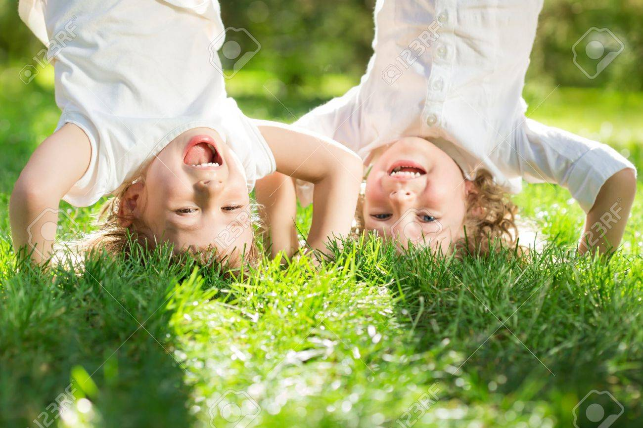 Happy children playing head over heels on green grass in spring park Stock Photo - 17642597