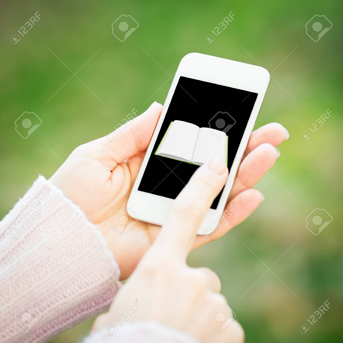 Smartphone with book in woman hands against green spring background Stock Photo - 18394769
