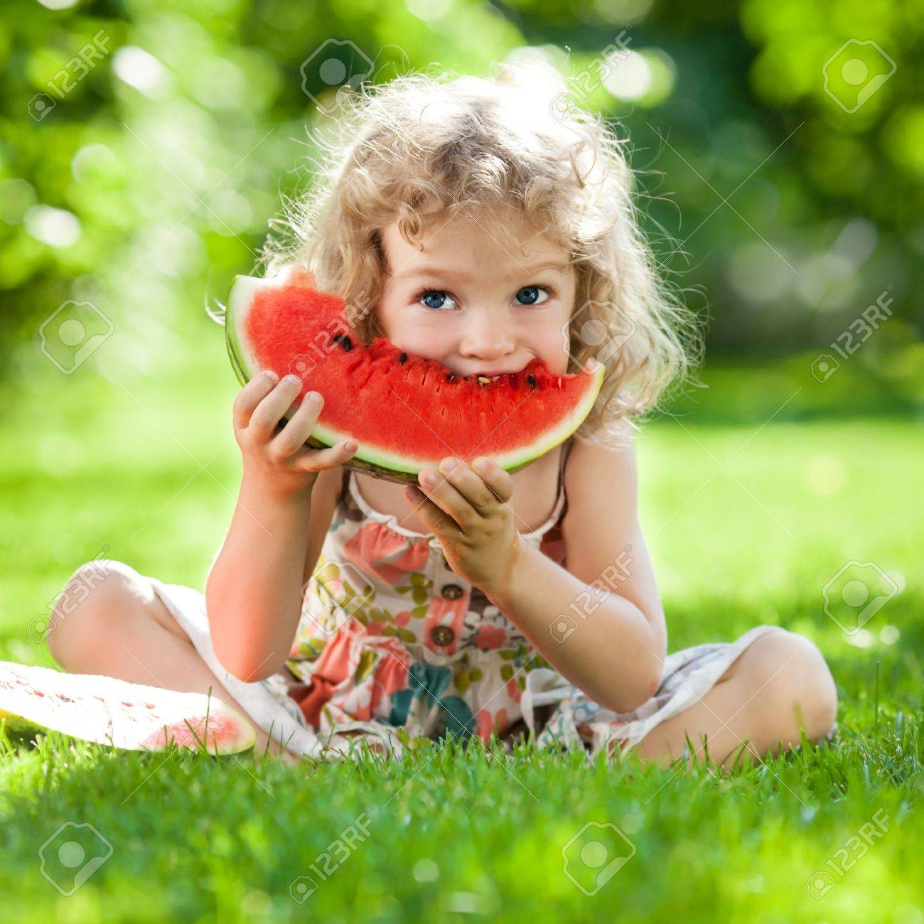 Happy child with big red slice of watermelon sitting on green grass in summer park Healthy eating concept - 18394776