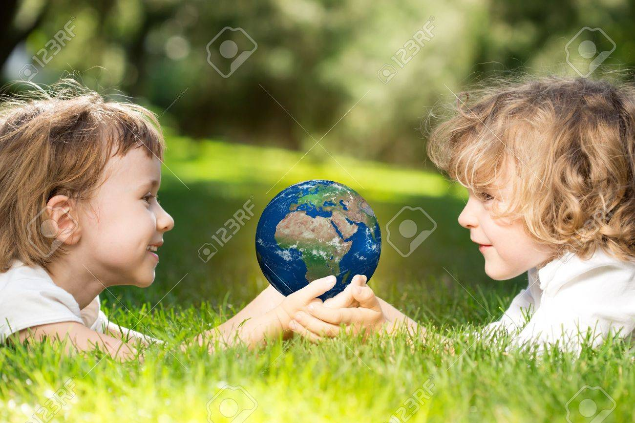 Children s holding world in hands against green spring background  Earth day concept Stock Photo - 18578076