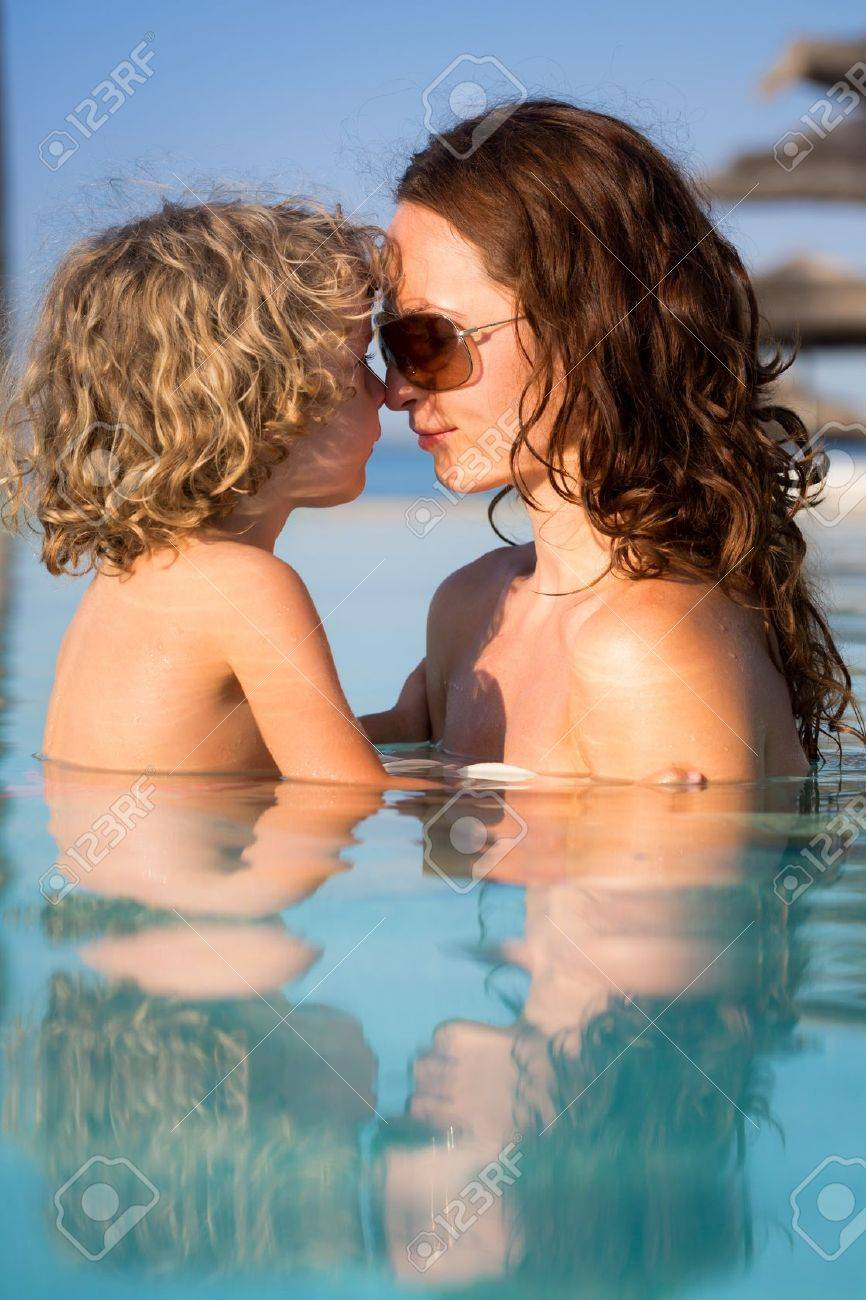 Smiling woman with child relaxing in swimming pool. Summer vacations concept Stock Photo - 19340736
