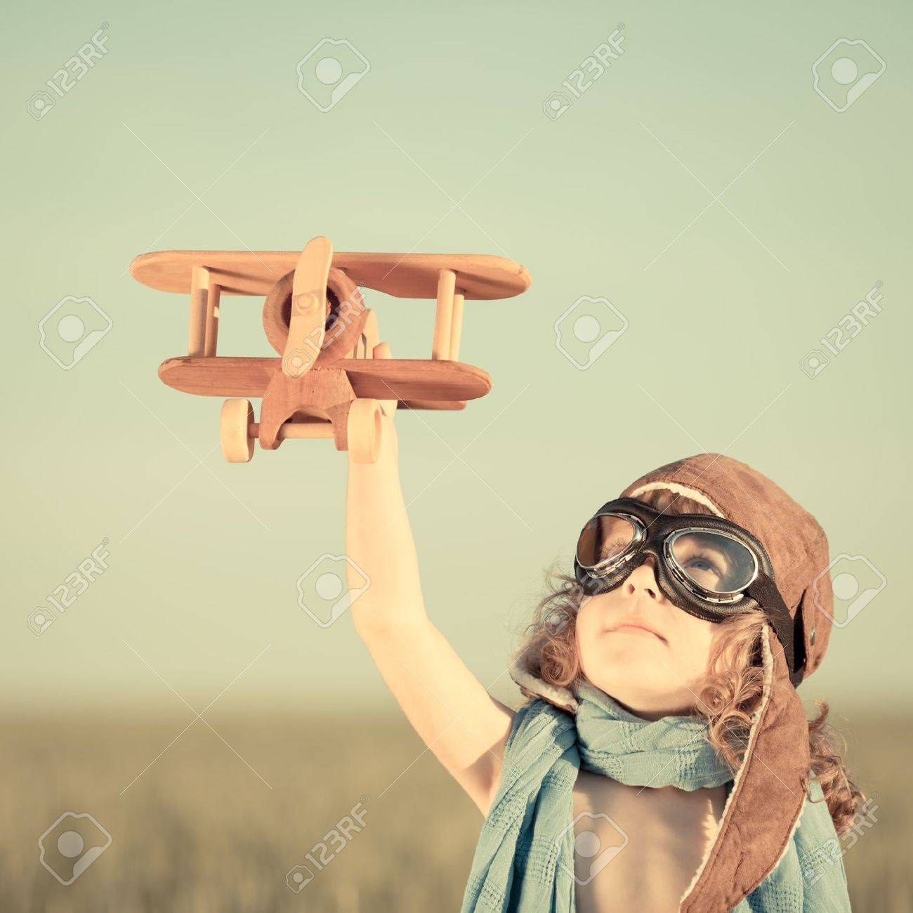 Happy kid playing with toy airplane against blue summer sky background Stock Photo - 19761824
