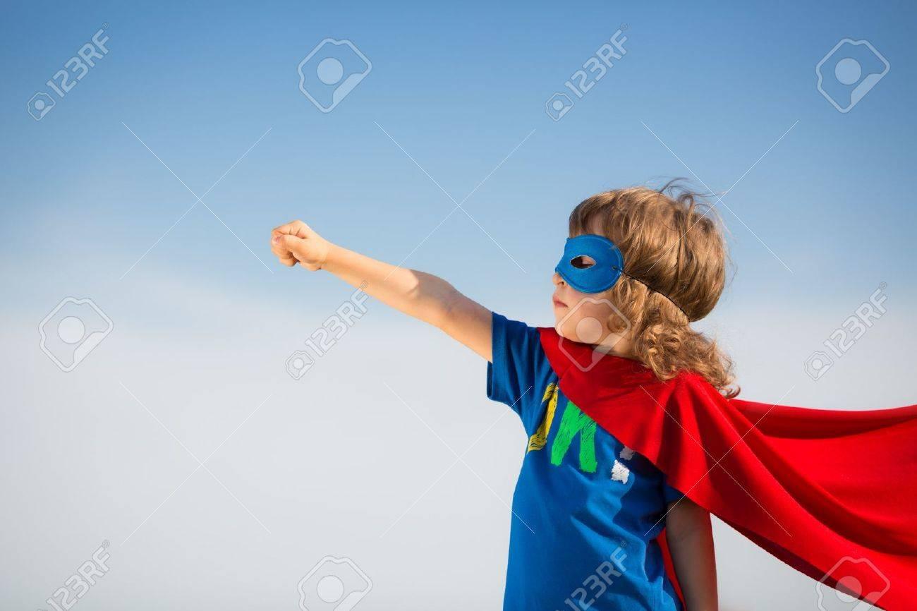 Superhero kid against blue sky background Stock Photo - 20409582