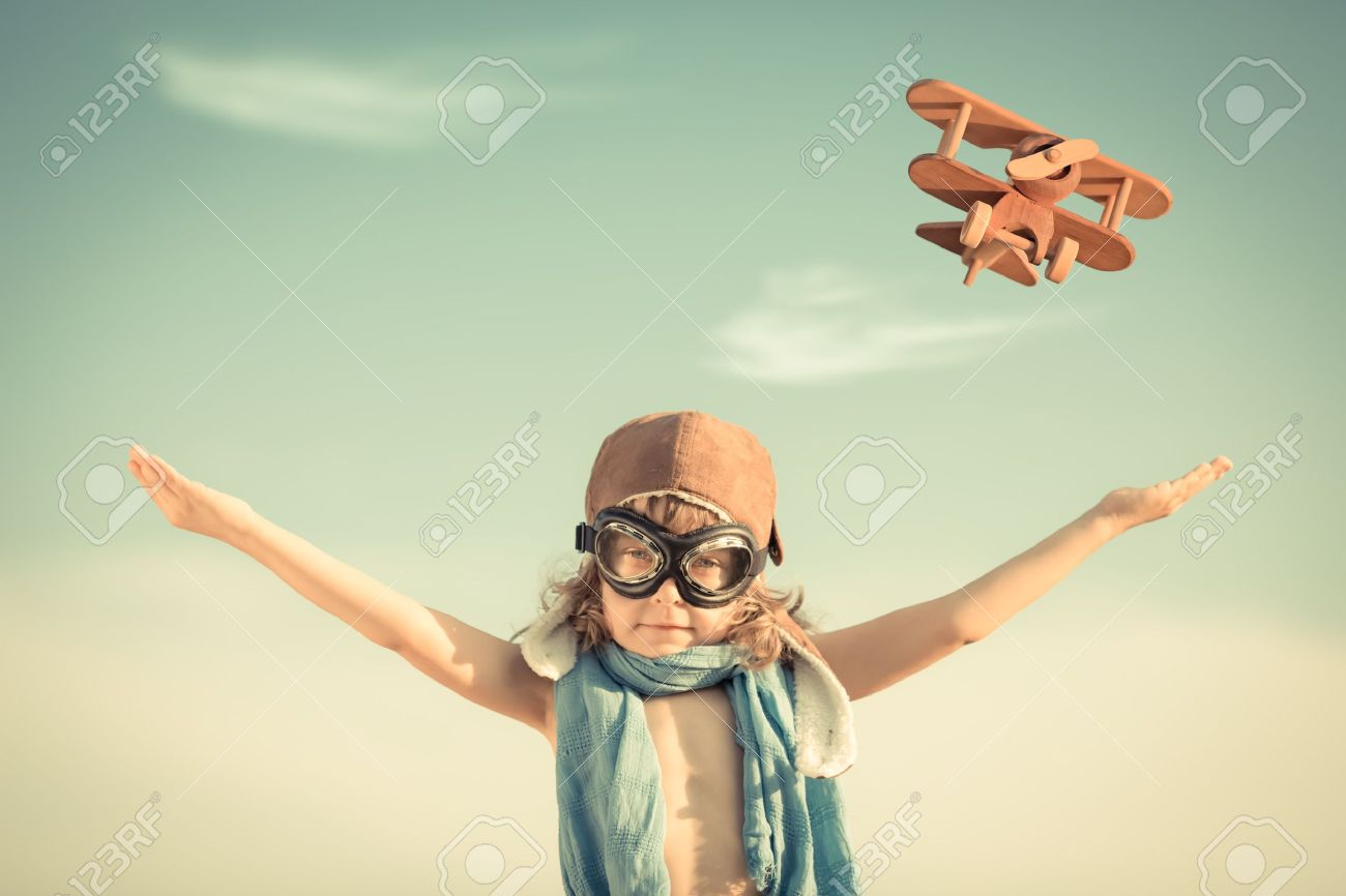 Happy kid playing with toy airplane against blue summer sky background Stock Photo - 20409576