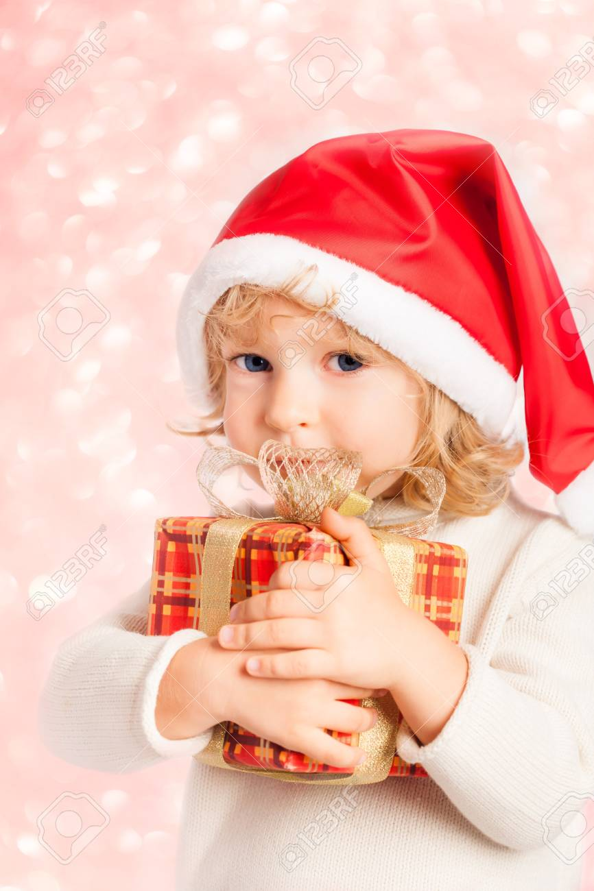 Happy baby holding gift box against Christmas ligths blurred background Stock Photo - 21503144