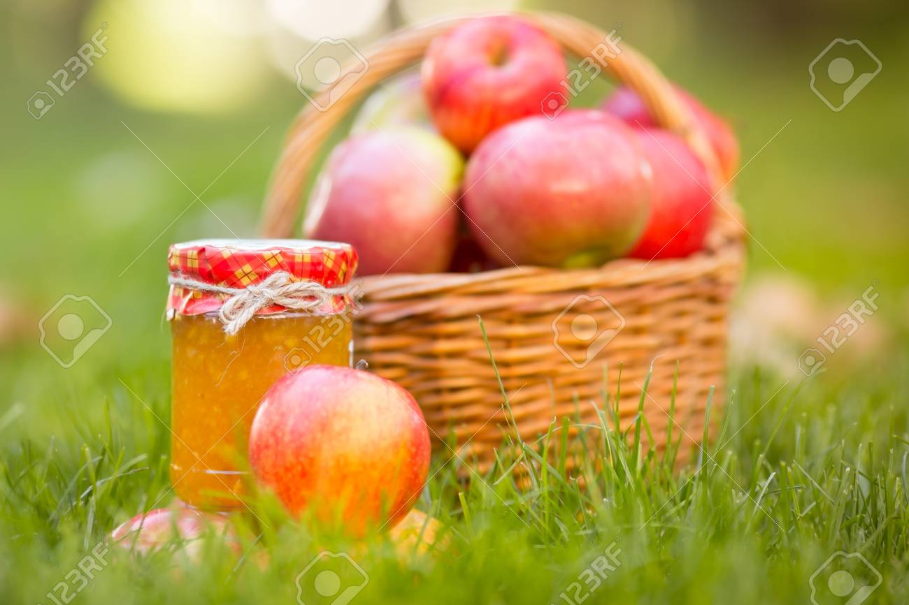 Basket with red apples and jam in autumn outdoors. Healthy eating concept Stock Photo - 22021848