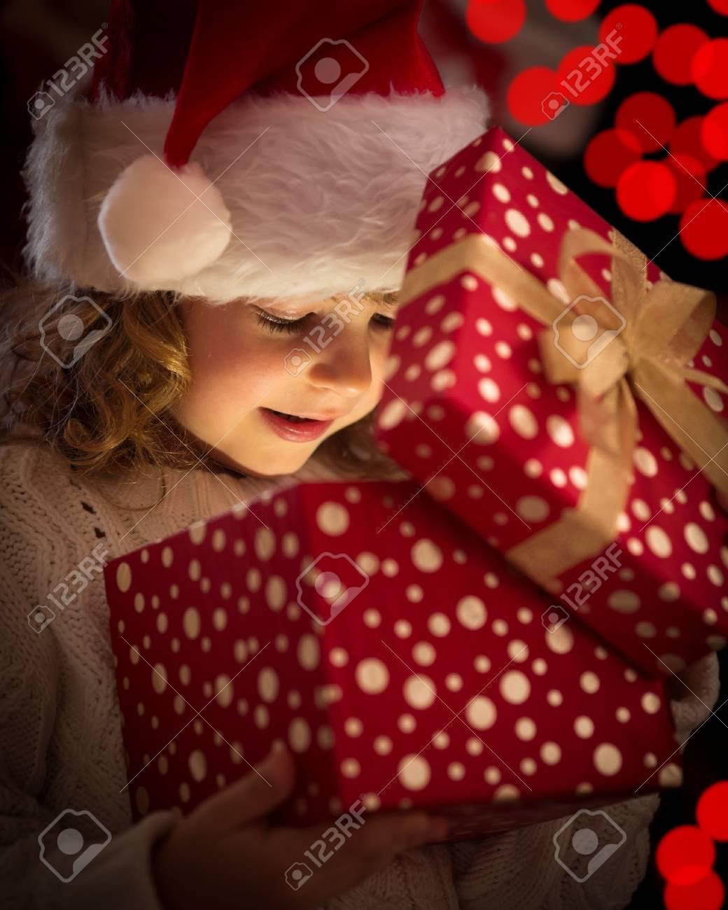 Happy child in Santa hat opening Christmas gift box Stock Photo - 23576182