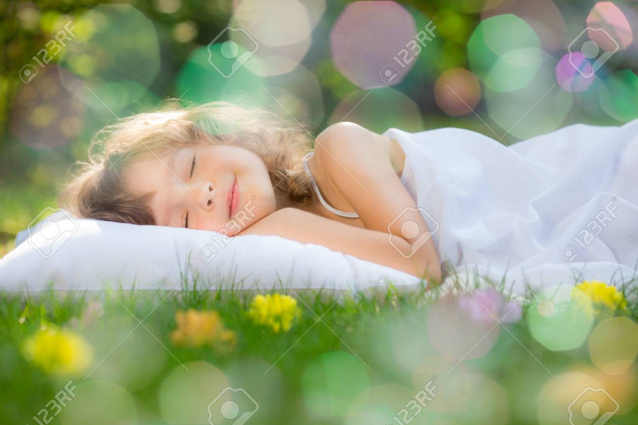Happy child sleeping on green grass outdoors in spring garden Stock Photo - 25222277