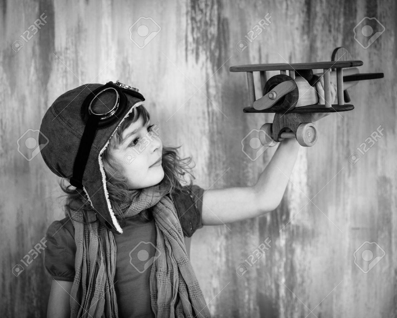 Gelukkig kind spelen met speelgoed houten vliegtuig binnen. zwart ...