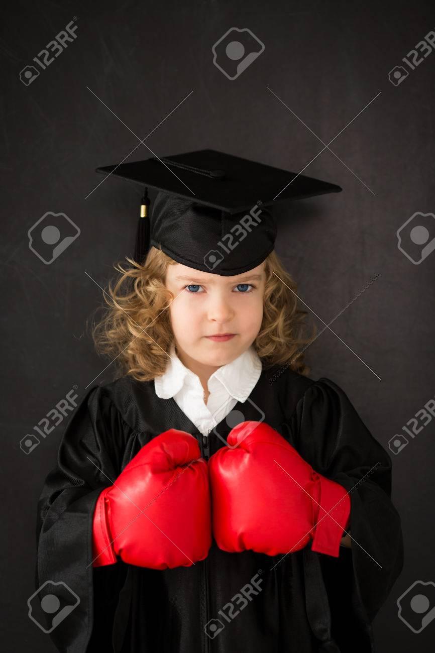 Smart kid in class wearing boxing gloves against blackboard Stock Photo - 30826156