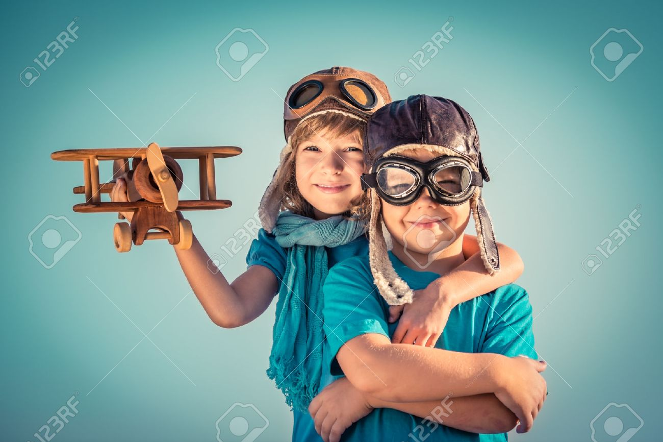 Happy kids playing with vintage wooden airplane outdoors. Portrait of children against summer sky background. Travel and freedom concept. Retro toned - 36091772