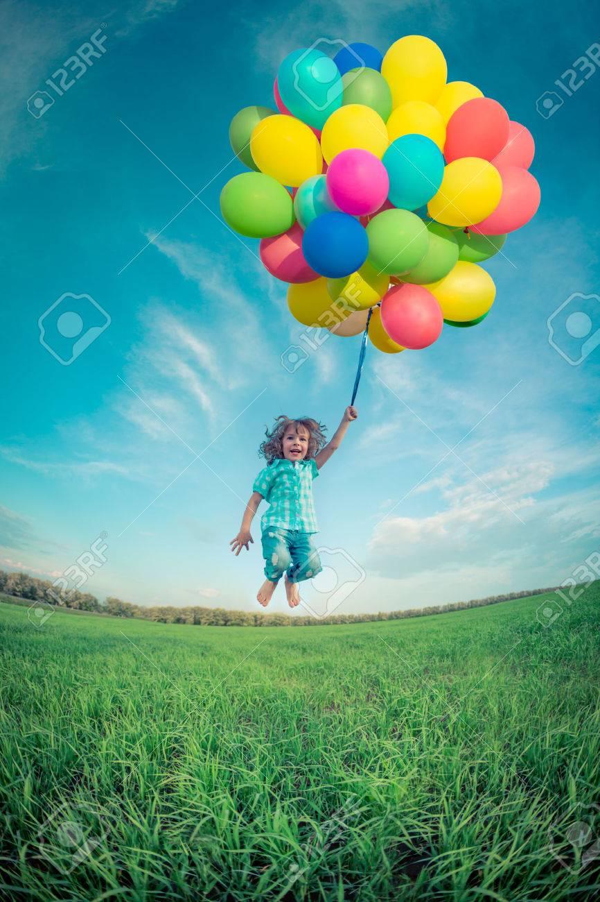 foto de archivo nio feliz saltando con globos coloridos juguetes al aire libre nio sonriente que se divierte en el campo de primavera verde contra el