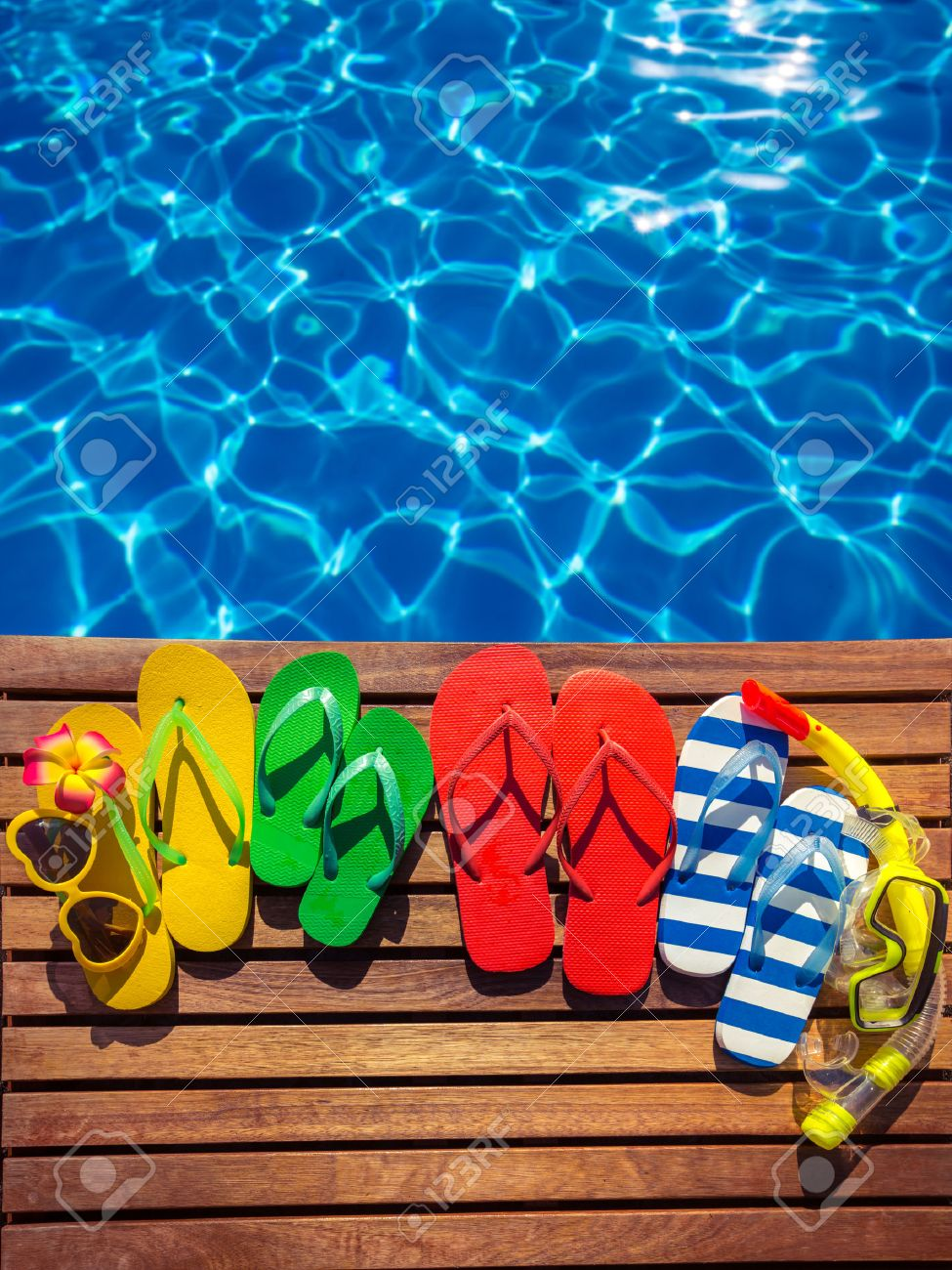 87ebdadff Multicolor flip-flops on wooden planks against blue water background.  Summer family vacation concept