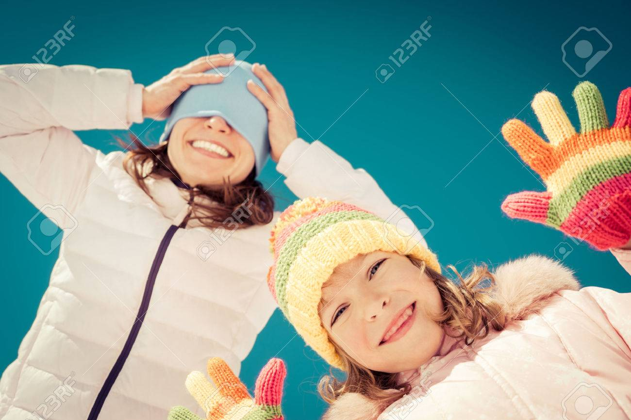 Happy family having fun outdoors in winter against blue sky background - 48654721