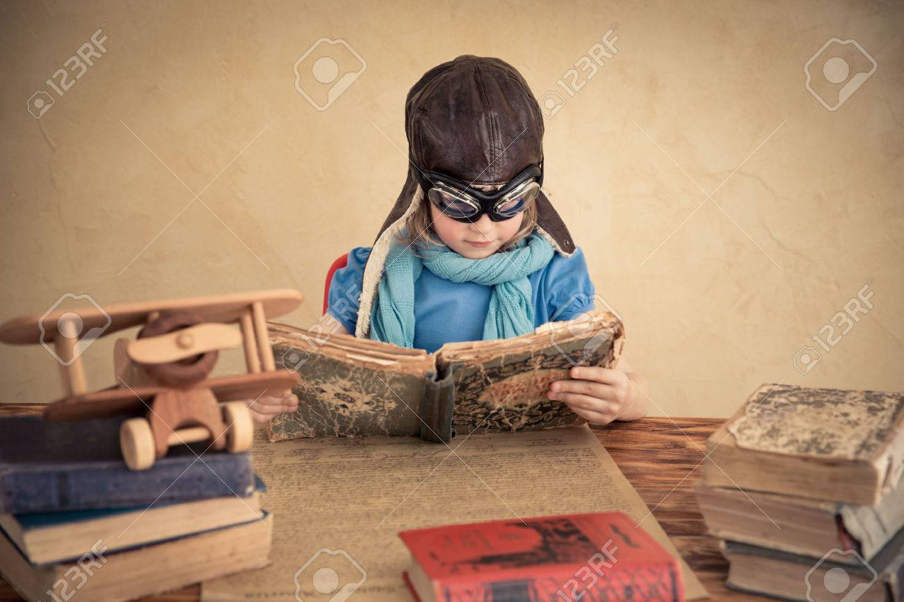 Child is pretending to be a pilot. Kid playing at home. Travel, freedom and imagination concept - 54490135