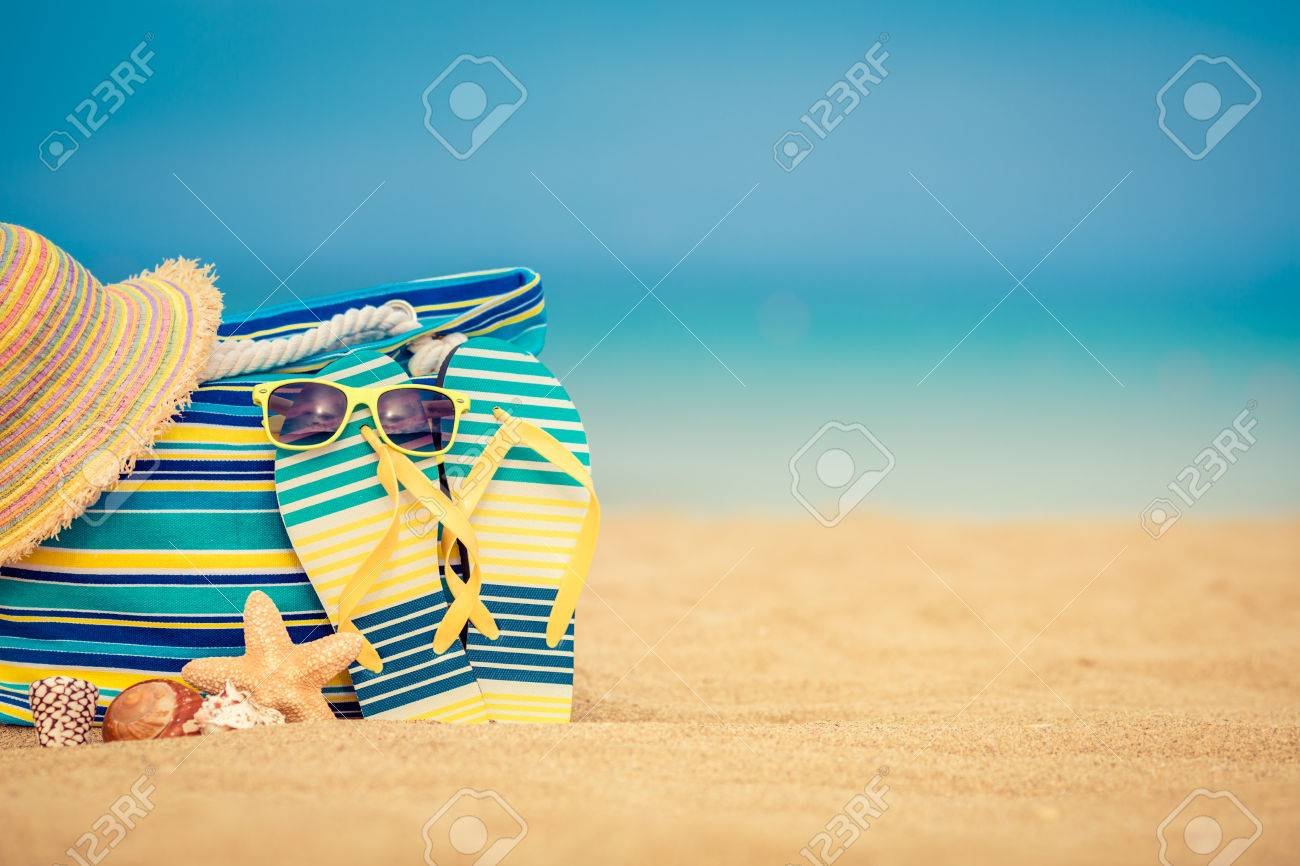 Flip-flops and bag on sandy beach against blue sea and sky background. Summer vacation concept - 56308636