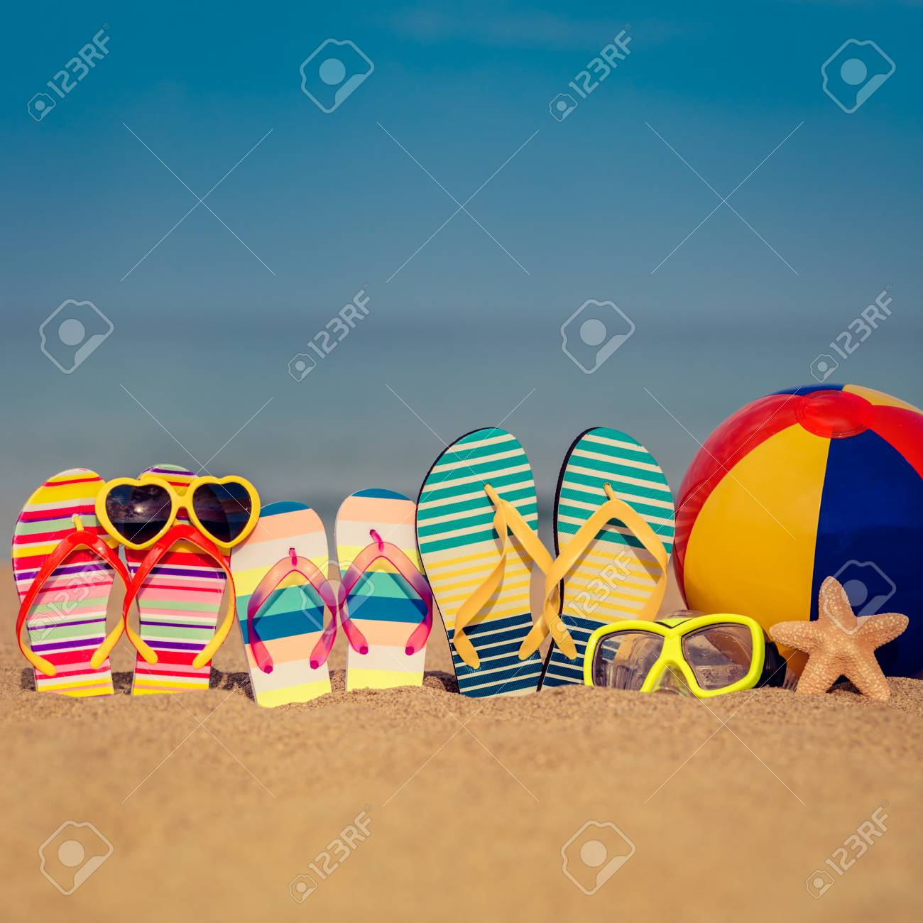 1352d6bc7735 Flip-flops on sandy beach against blue sea and sky background. Summer  vacation concept