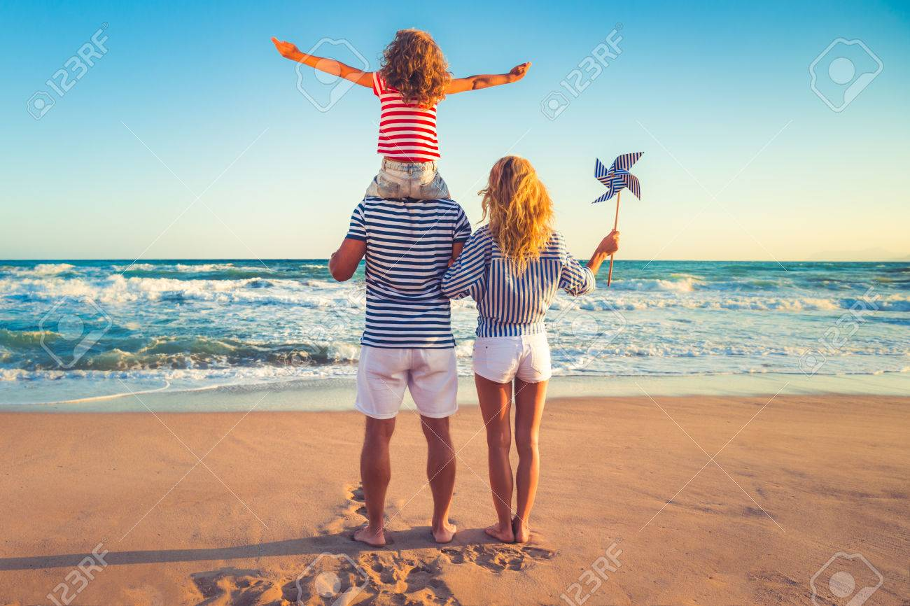Happy family on the beach. People having fun on summer vacation. Father, mother and child against blue sea and sky background. Holiday travel concept - 78281259