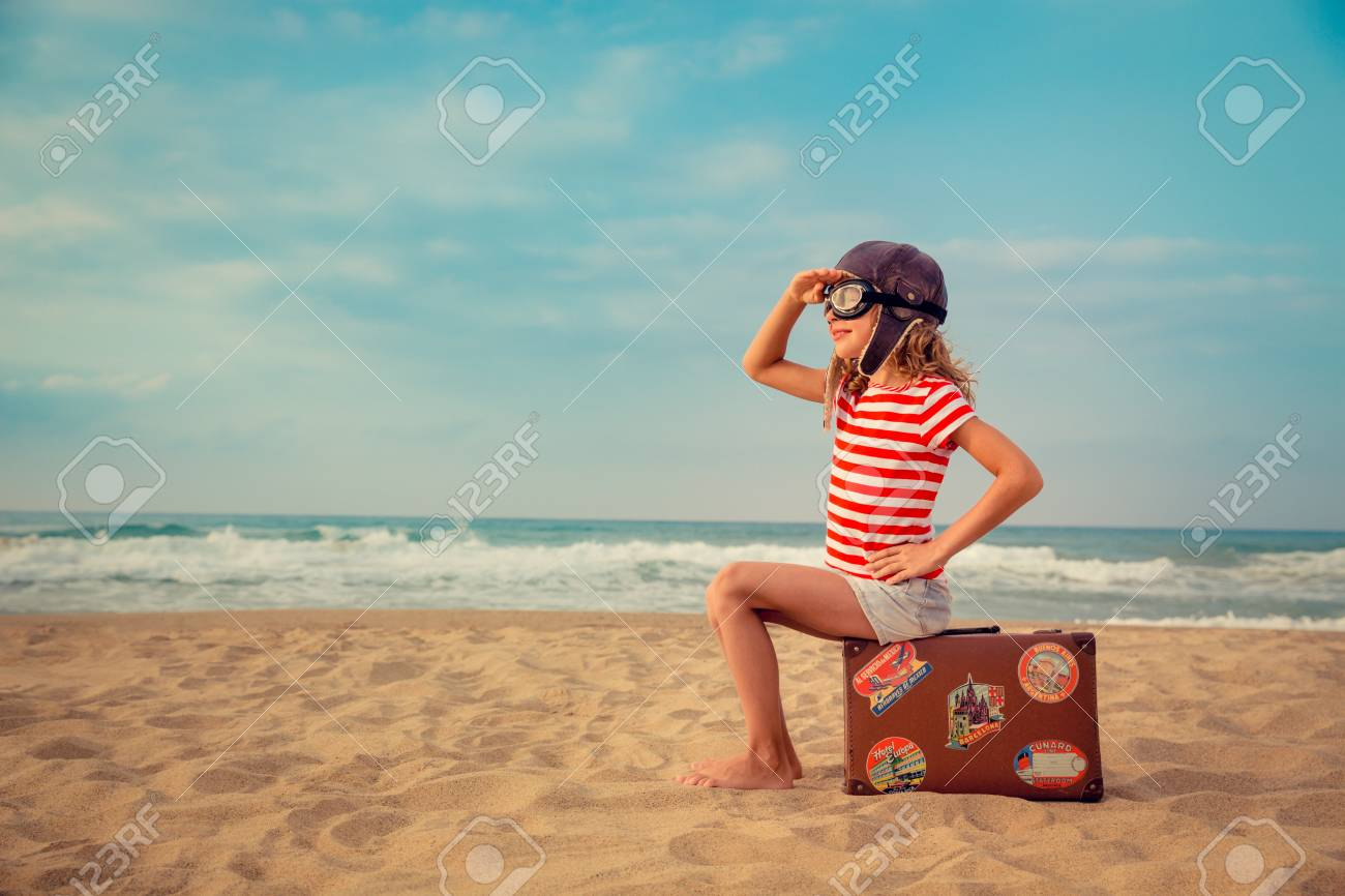 Happy child playing with toy airplane against sea and sky background. Kid pilot having fun outdoor. Summer vacation and travel concept. Freedom and imagination - 78586819