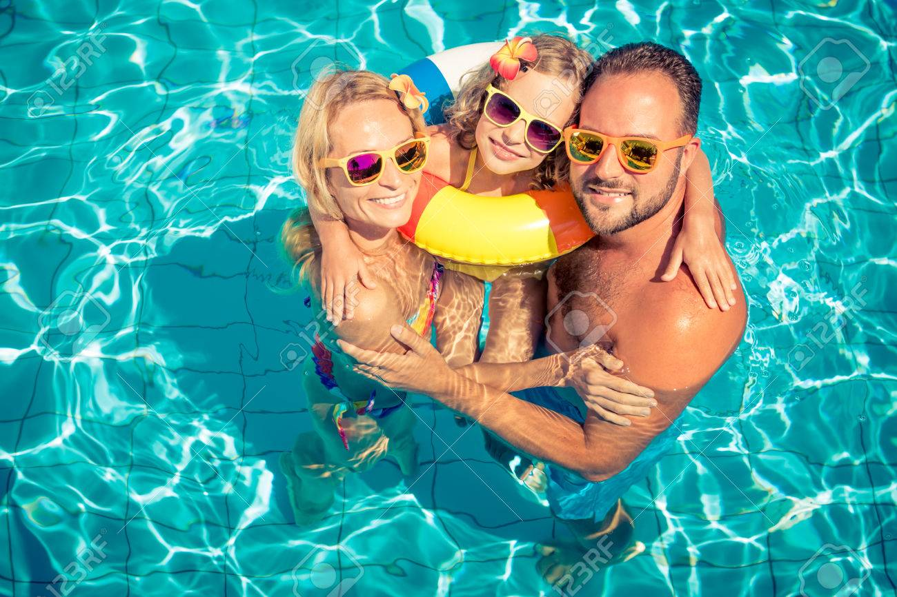 Happy family having fun on summer vacation. Father, mother and child playing in swimming pool. Active healthy lifestyle concept - 78453790