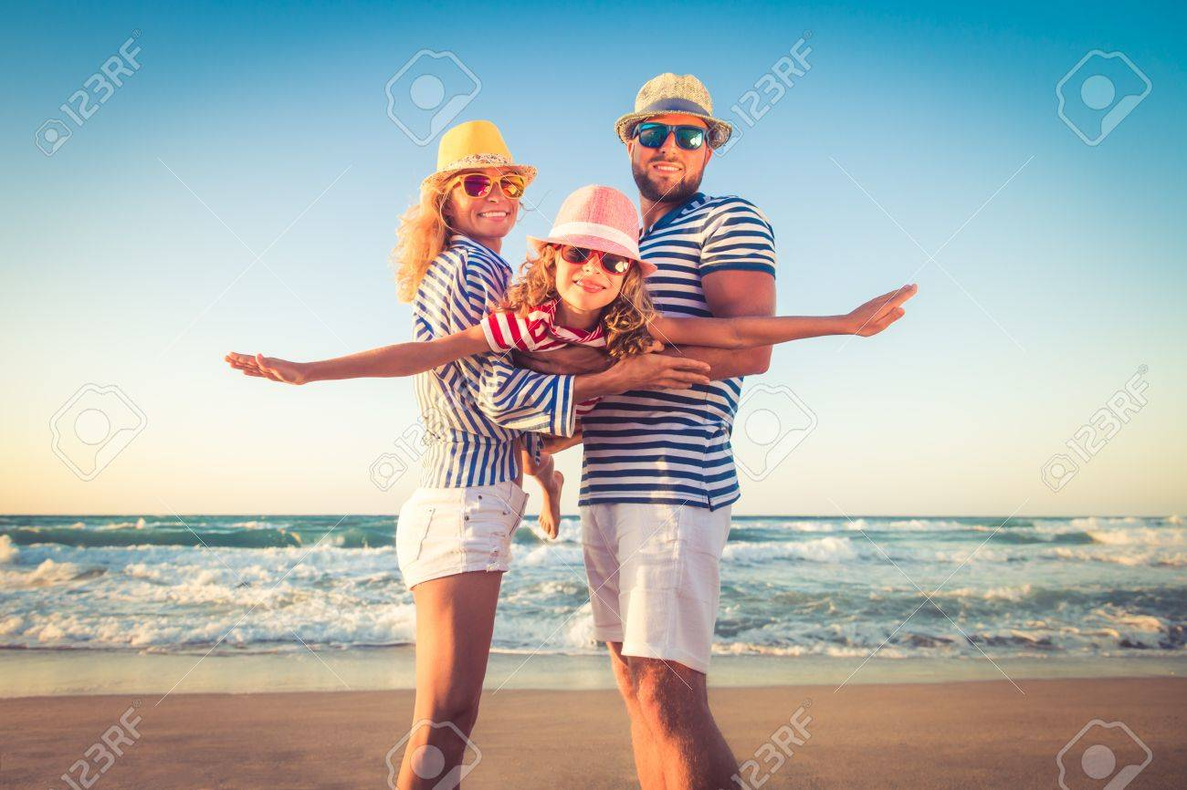 Happy family on the beach. People having fun on summer vacation. Father, mother and child against blue sea and sky background. Holiday travel concept - 78590207
