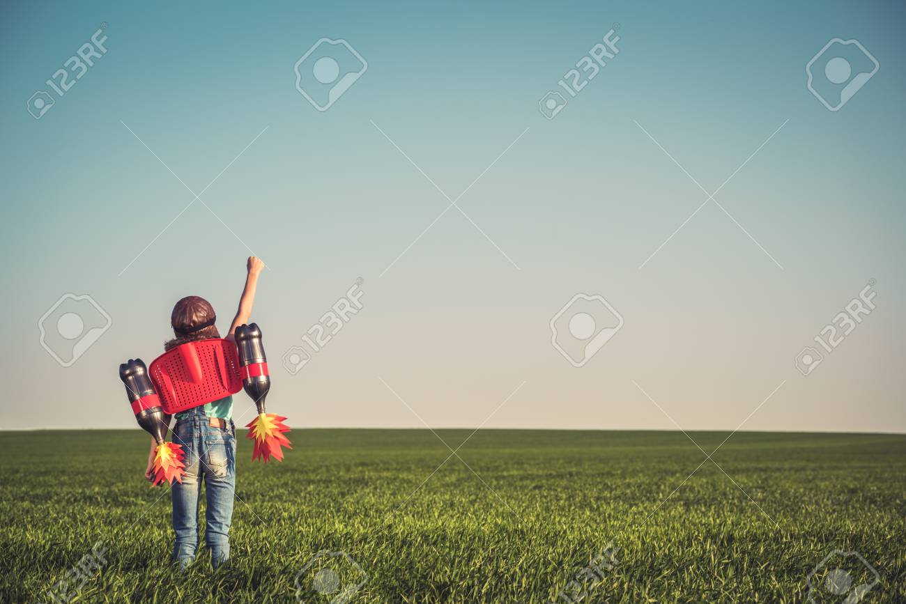 Kid with jet pack outdoor. Child playing in green spring field. Success, imagination and innovation technology concept. Summer travel and adventure - 78755393