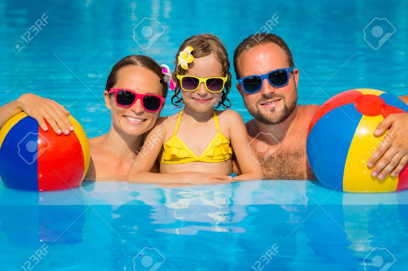 Happy family having fun on summer vacation. Father, mother and child playing in swimming pool. Active healthy lifestyle concept - 79035664