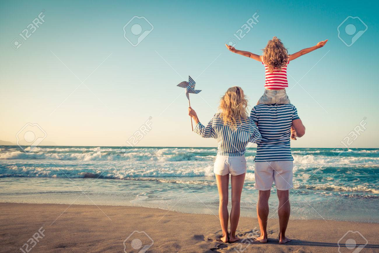 Happy family on the beach. People having fun on summer vacation. Father, mother and child against blue sea and sky background. Holiday travel concept - 79035672