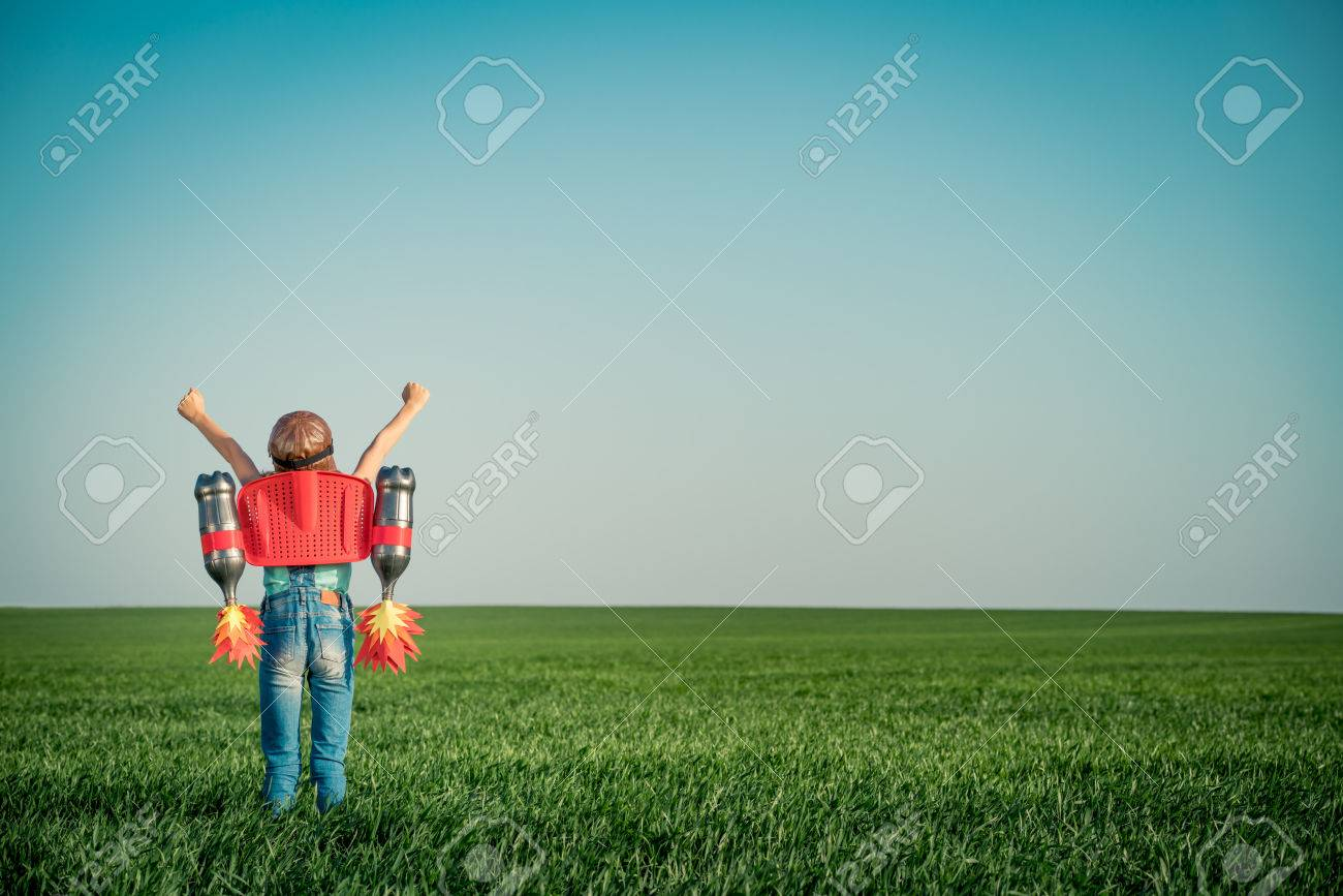 Kid with jet pack outdoor. Child playing in green spring field. Success, imagination and innovation technology concept. Summer travel and adventure - 79035711