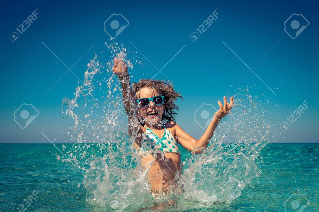 Happy child playing in the sea. Kid having fun at the beach. Summer vacation and active lifestyle concept - 80327397