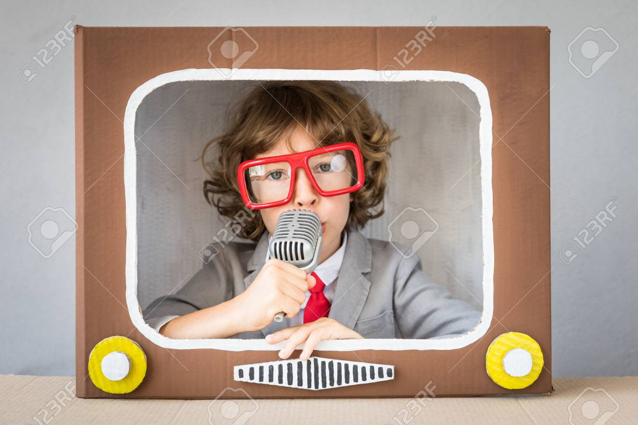 Child playing with cardboard box TV. Kid having fun at home. Communication concept - 83655731