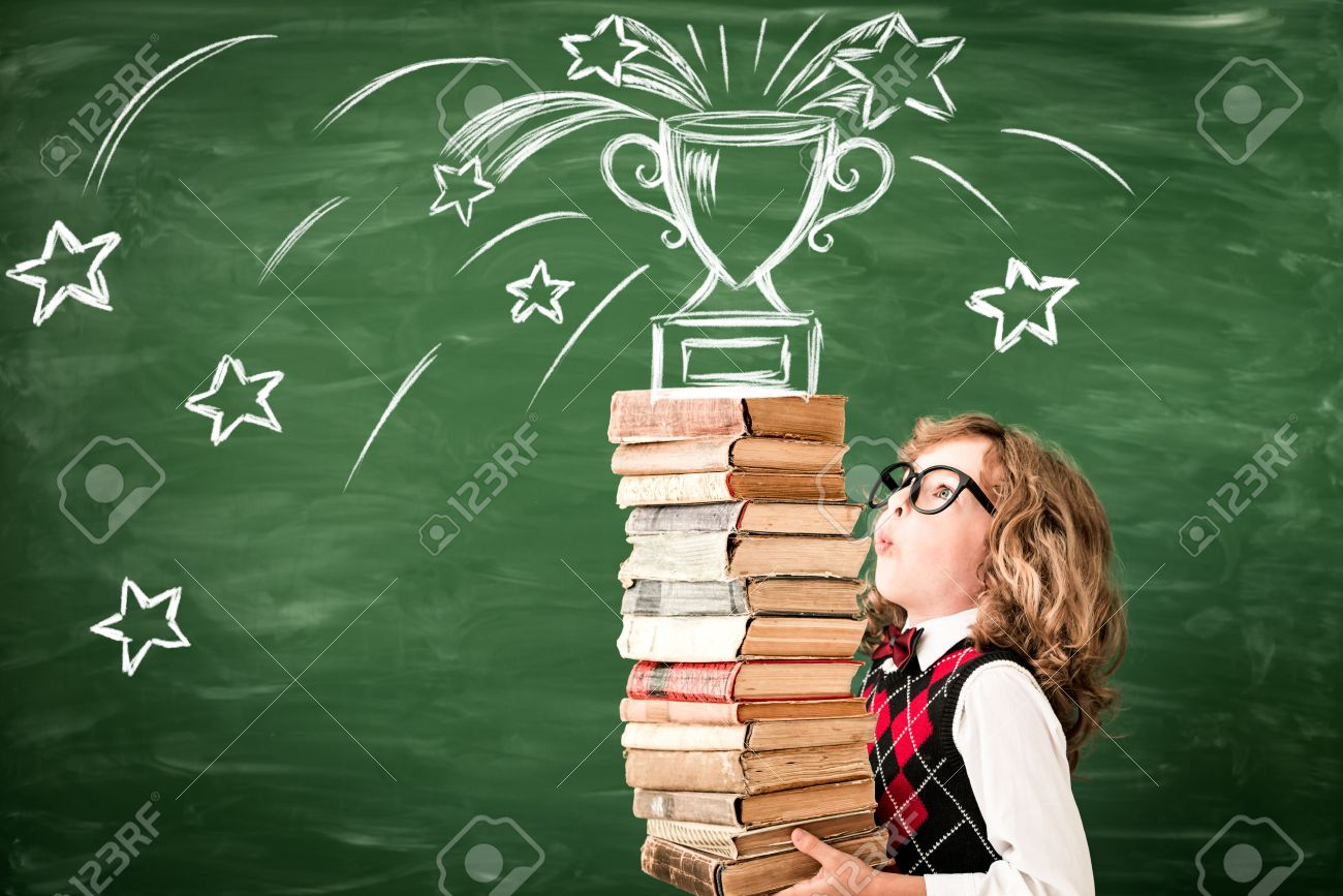 Portrait of child in classroom against chalkboard. Kid with books in class. Success, idea and win concept. Back to school - 83655741