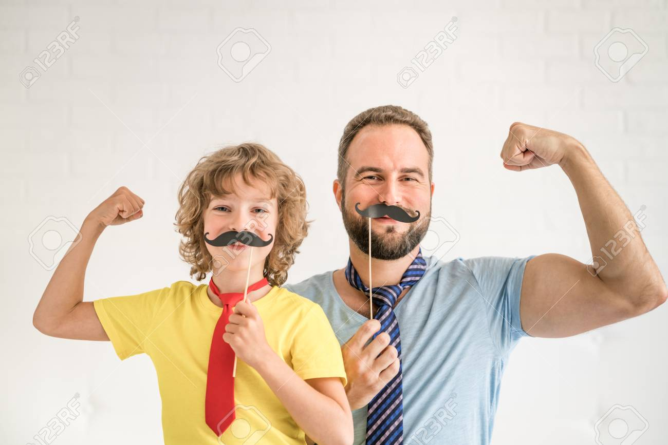 Funny man and kid with fake mustache. Happy family playing in home - 87262495