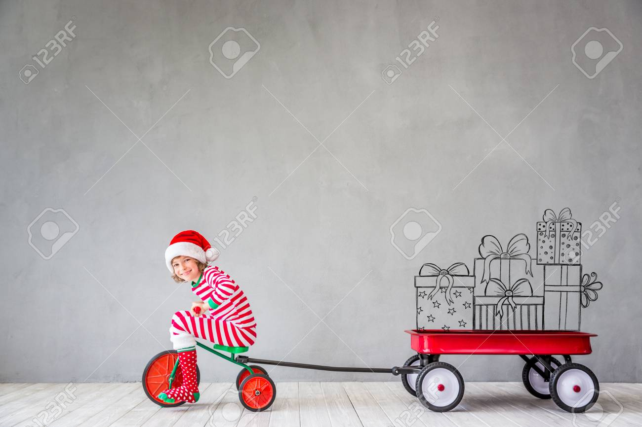 Happy child in Christmas time. Funny kid playing at home. Xmas winter holiday concept - 88269361