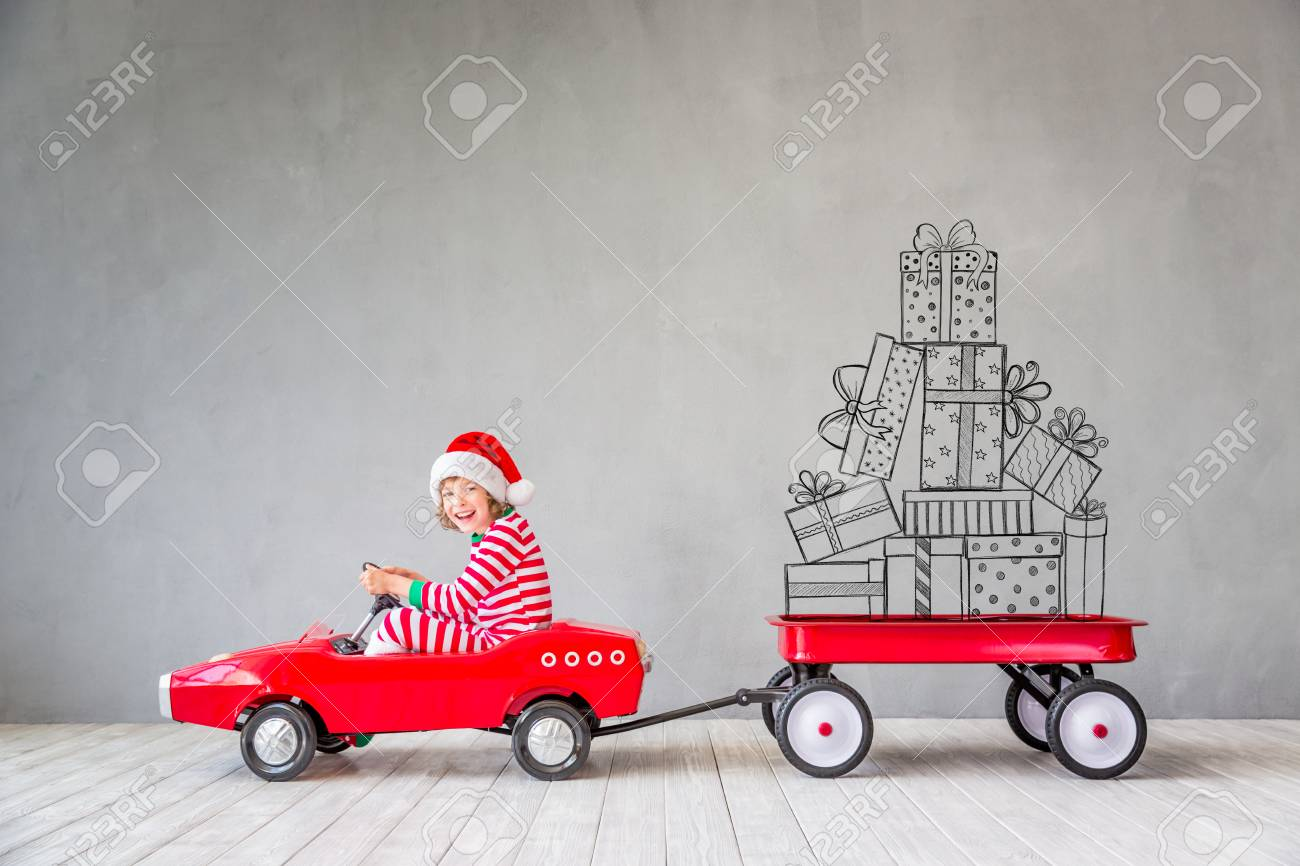 Happy child with Christmas gift. Kid having fun at home. Xmas holiday concept - 88269400