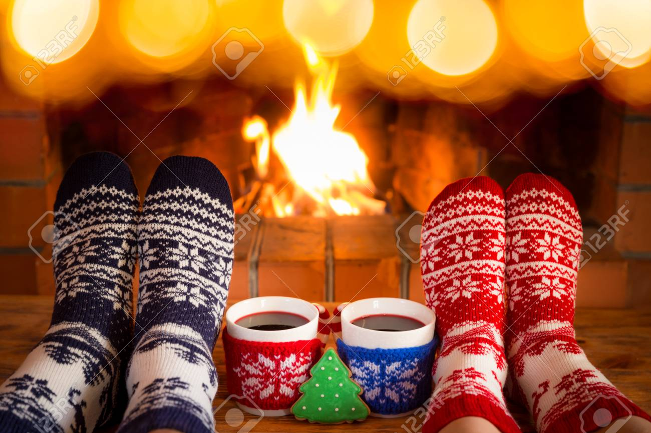Couple in Christmas socks near fireplace. Friends having fun together. People relaxing at home. Winter holiday Xmas and New Year concept - 90370154