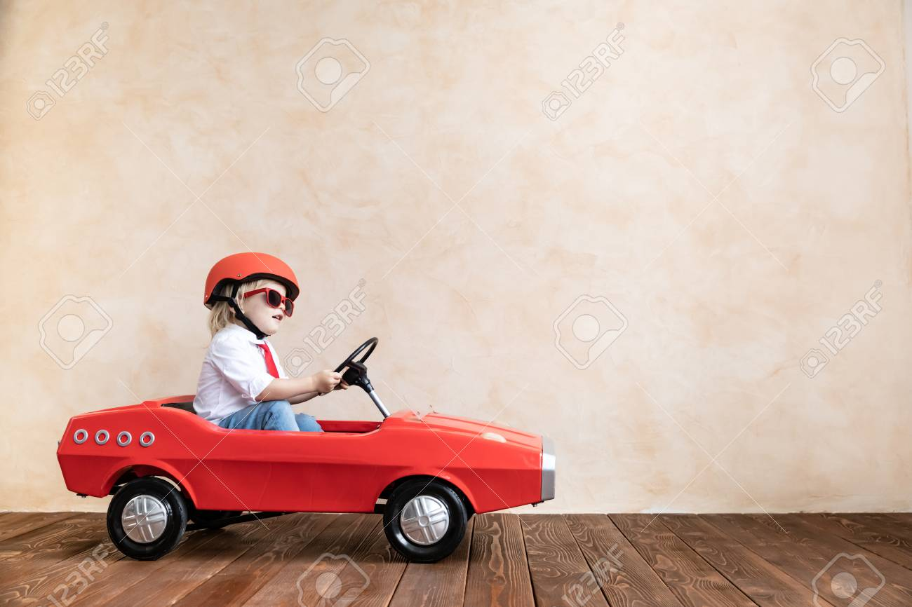 Happy child playing at home. Funny kid driving toy car indoor. Success and win concept - 120403070