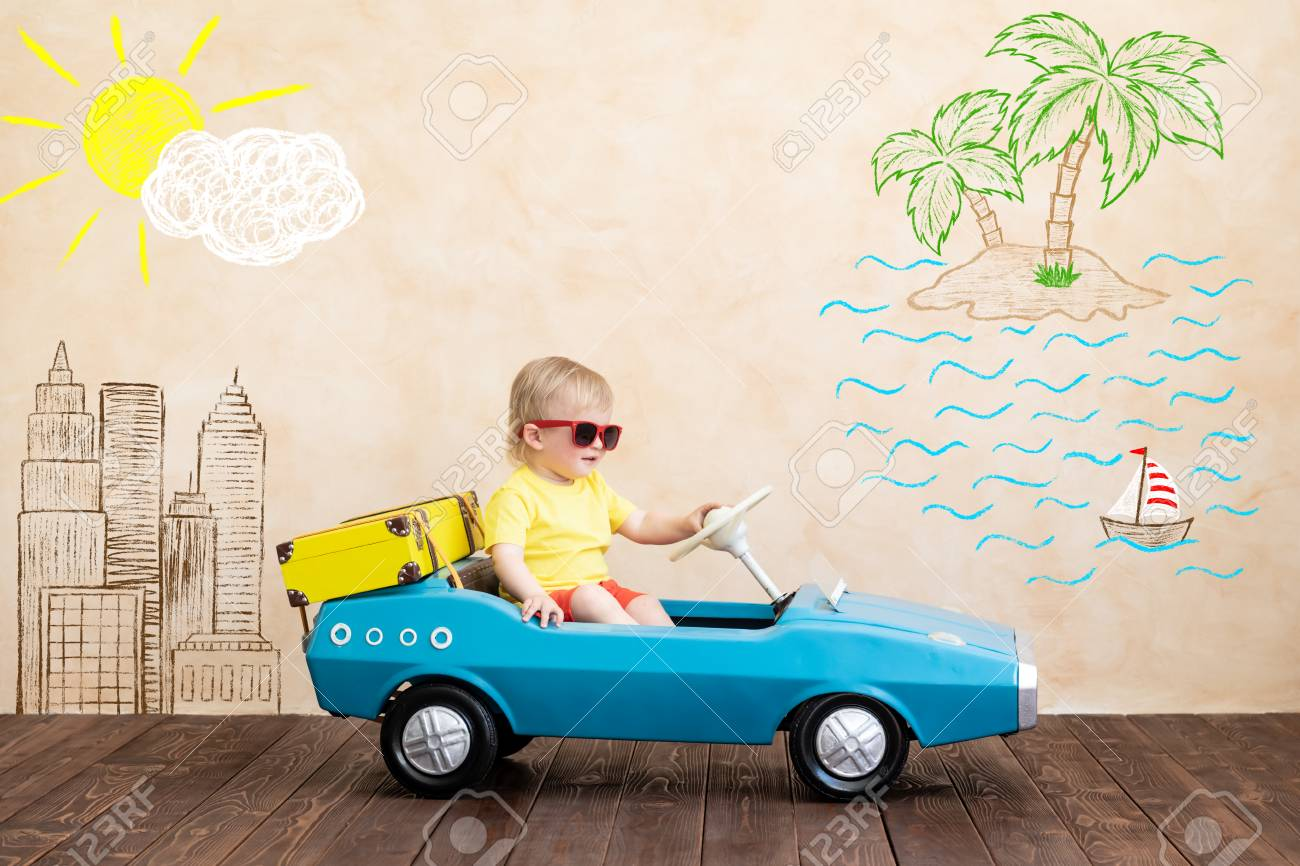 Happy child riding toy vintage car. Funny kid playing at home. Summer vacation and travel concept - 120982108