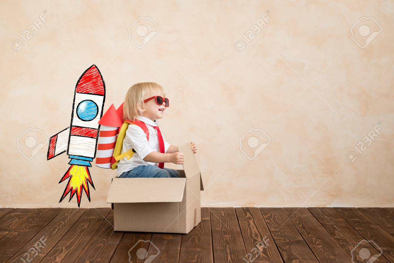 Happy child playing with toy rocket at home. Funny kid driving cardboard box indoor. Success and win concept - 120982117