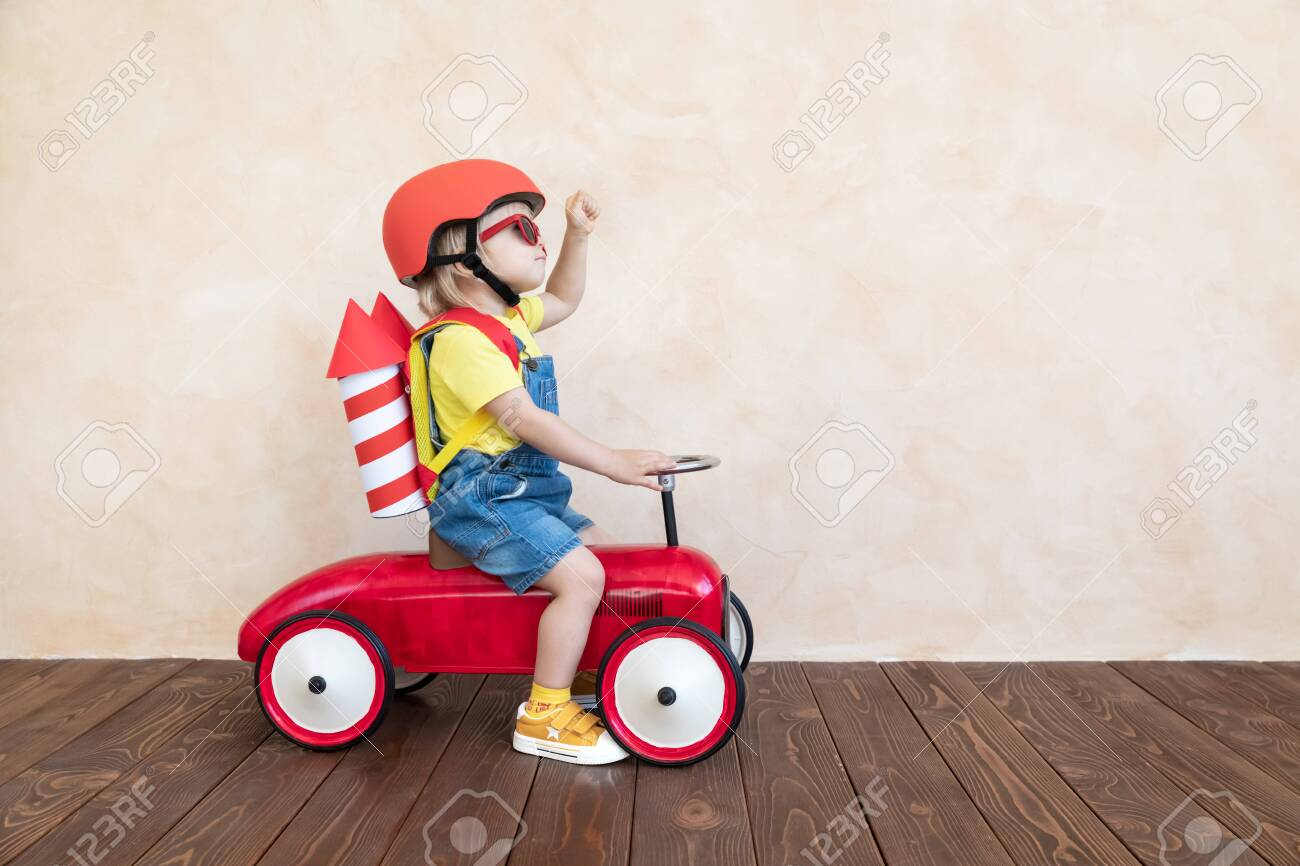 Kid with toy paper rocket. Child playing at home. Success, imagination and innovation technology concept - 122555634