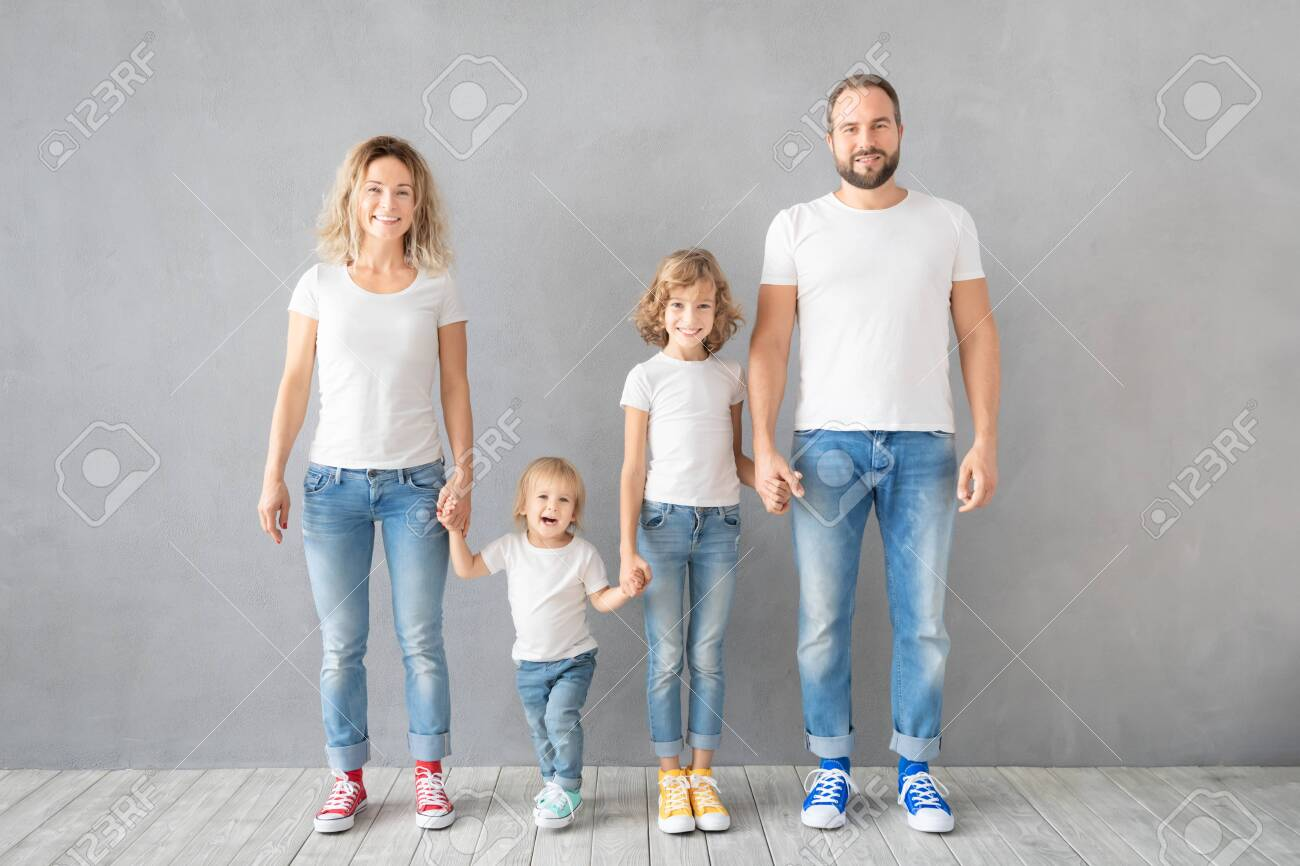 Happy family standing against grey background. Parents with children having fun at home. Portrait of father, mother, daughter and son - 131137595