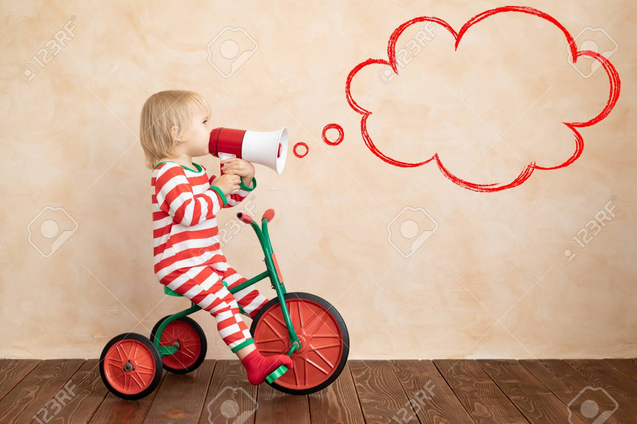 Happy child dressed Santa Claus costume playing at home. Funny kid driving toy car and speaking by megaphone. Christmas holiday concept - 131136937