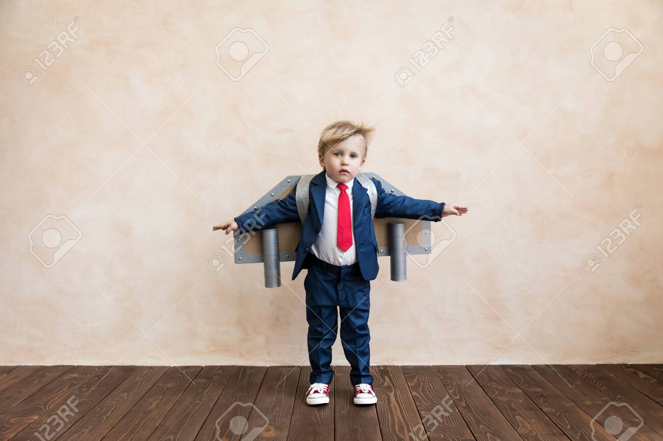 Portrait of young businessman with toy paper wings. Happy child playing at home. Kid having fun. Success, creative and start up concept - 133715886