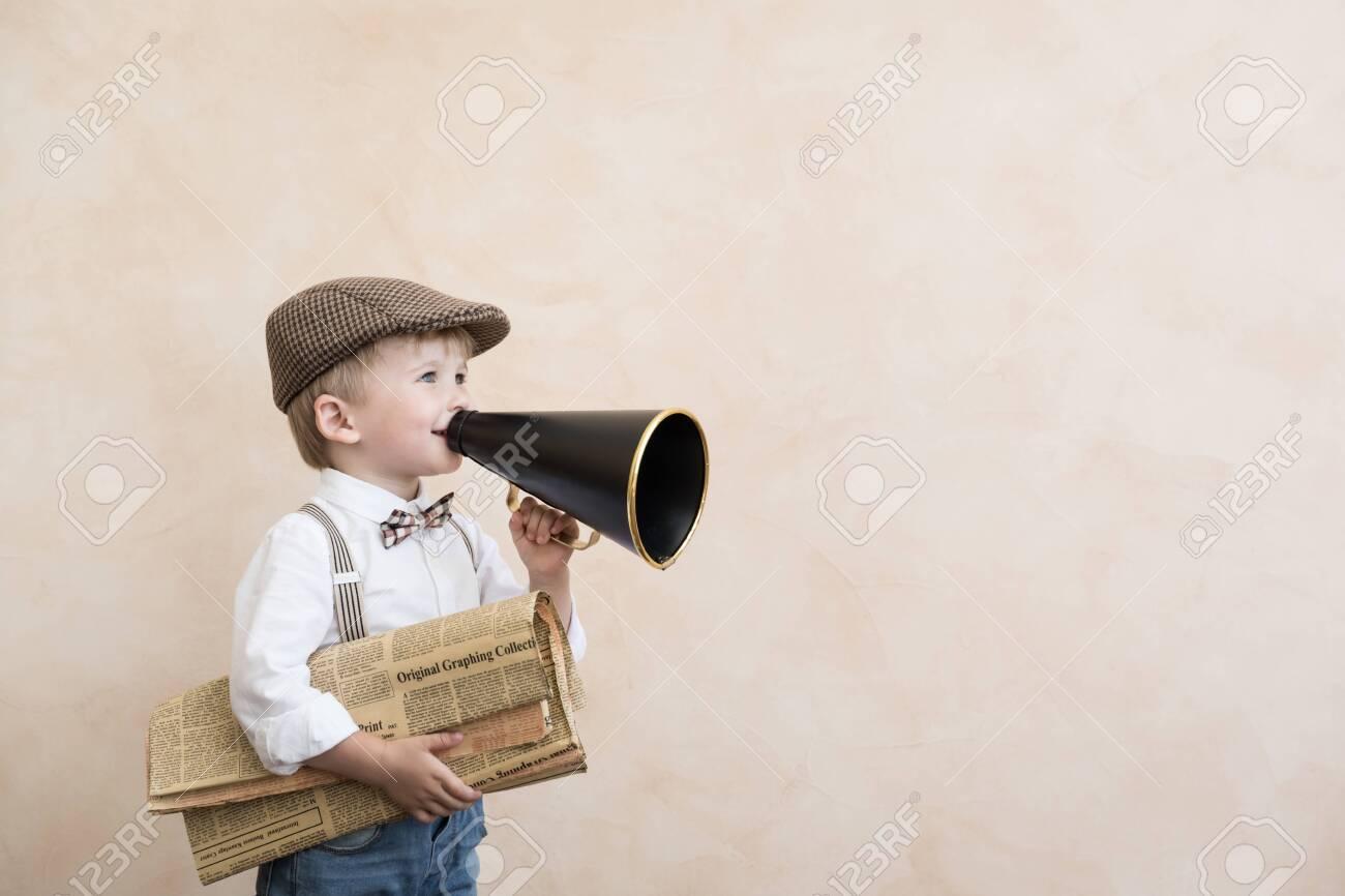 Child holding loudspeaker and newspaper. Kid shouting through vintage megaphone. Business news concept - 133715871