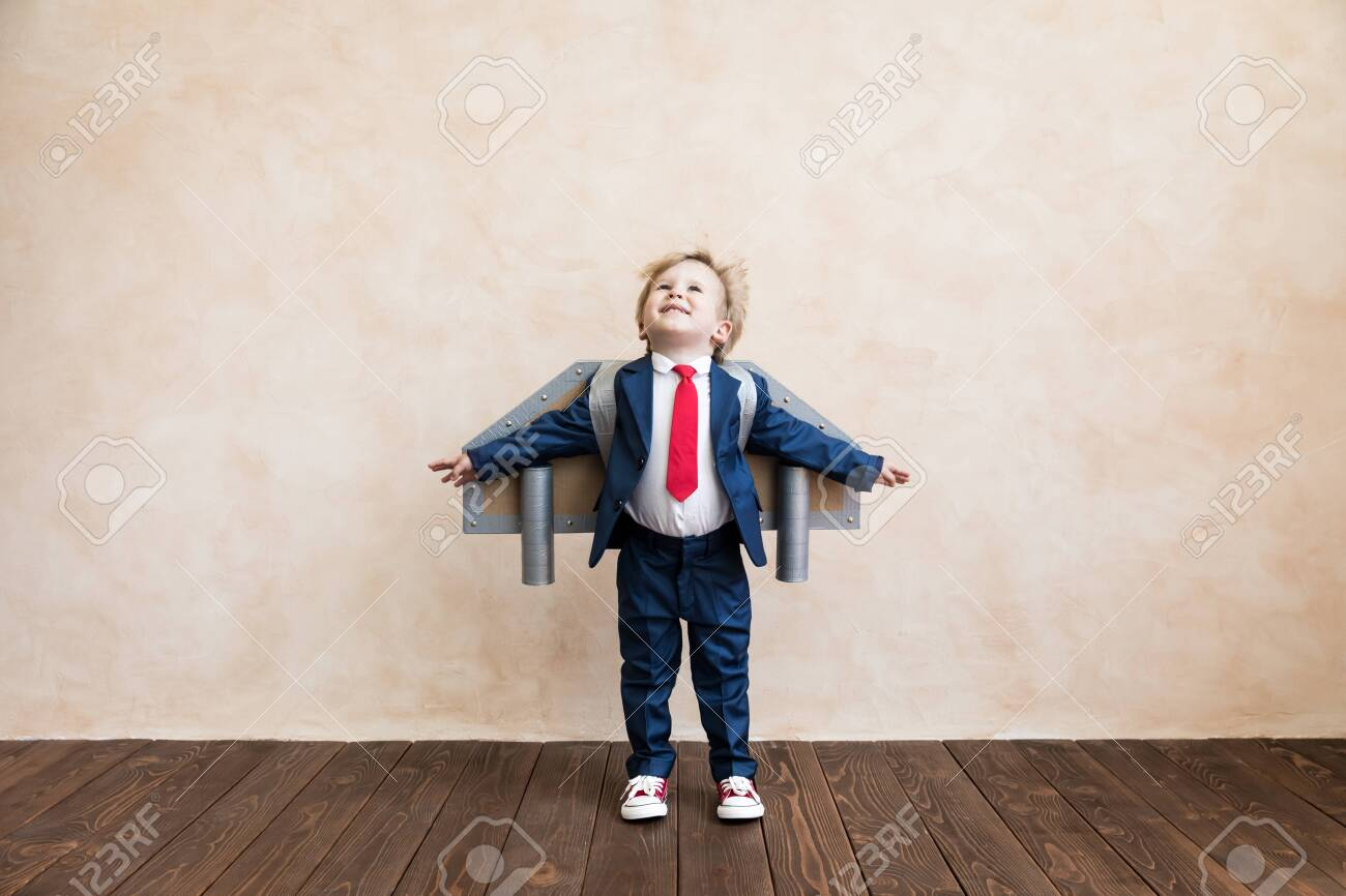 Portrait of young businessman with toy paper wings. Happy child playing at home. Kid having fun. Success, creative and start up concept - 133929429