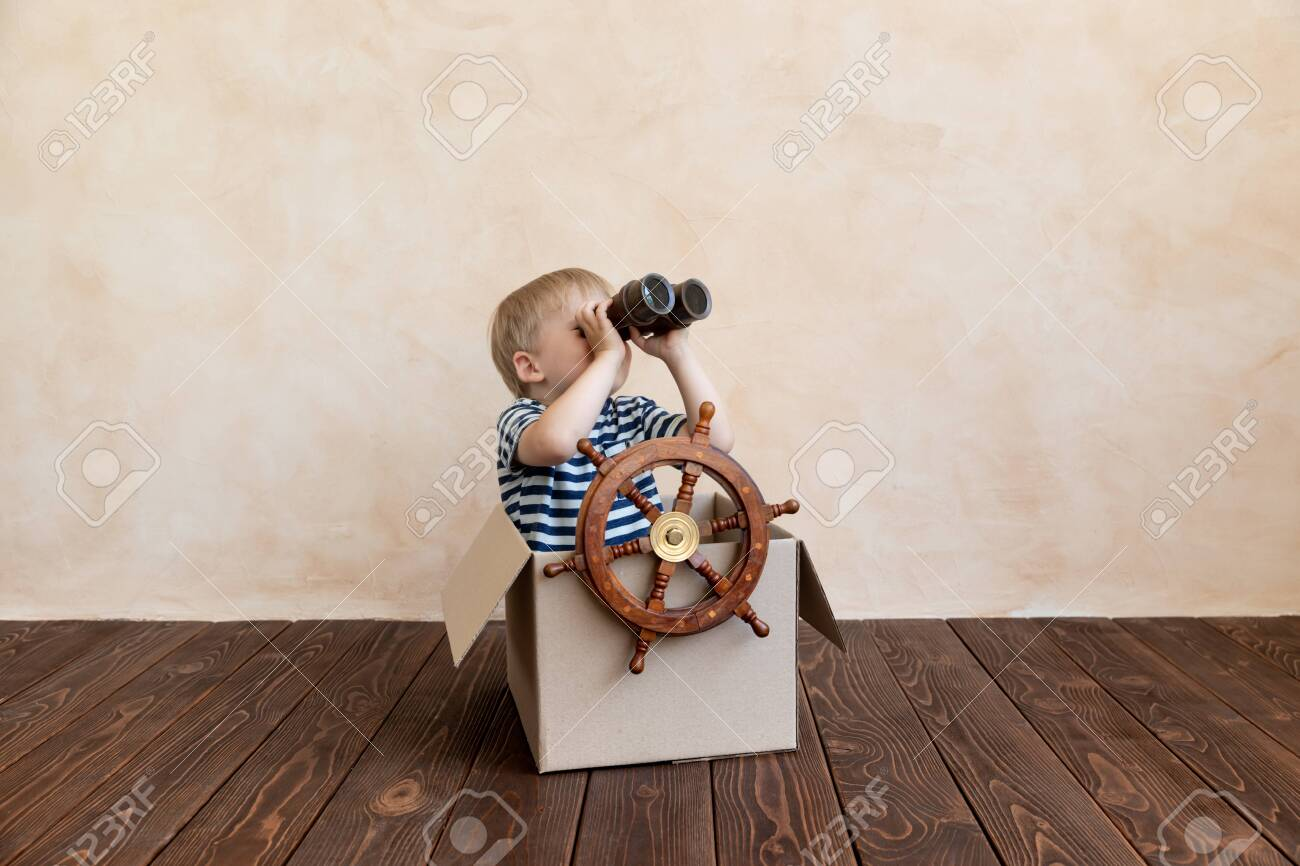 Happy child dreams of becoming a captain. Kid having fun at home. Boy wearing striped shirt playing in cardboard box. Summer vacation and travel concept. Dream and imagination - 140433355