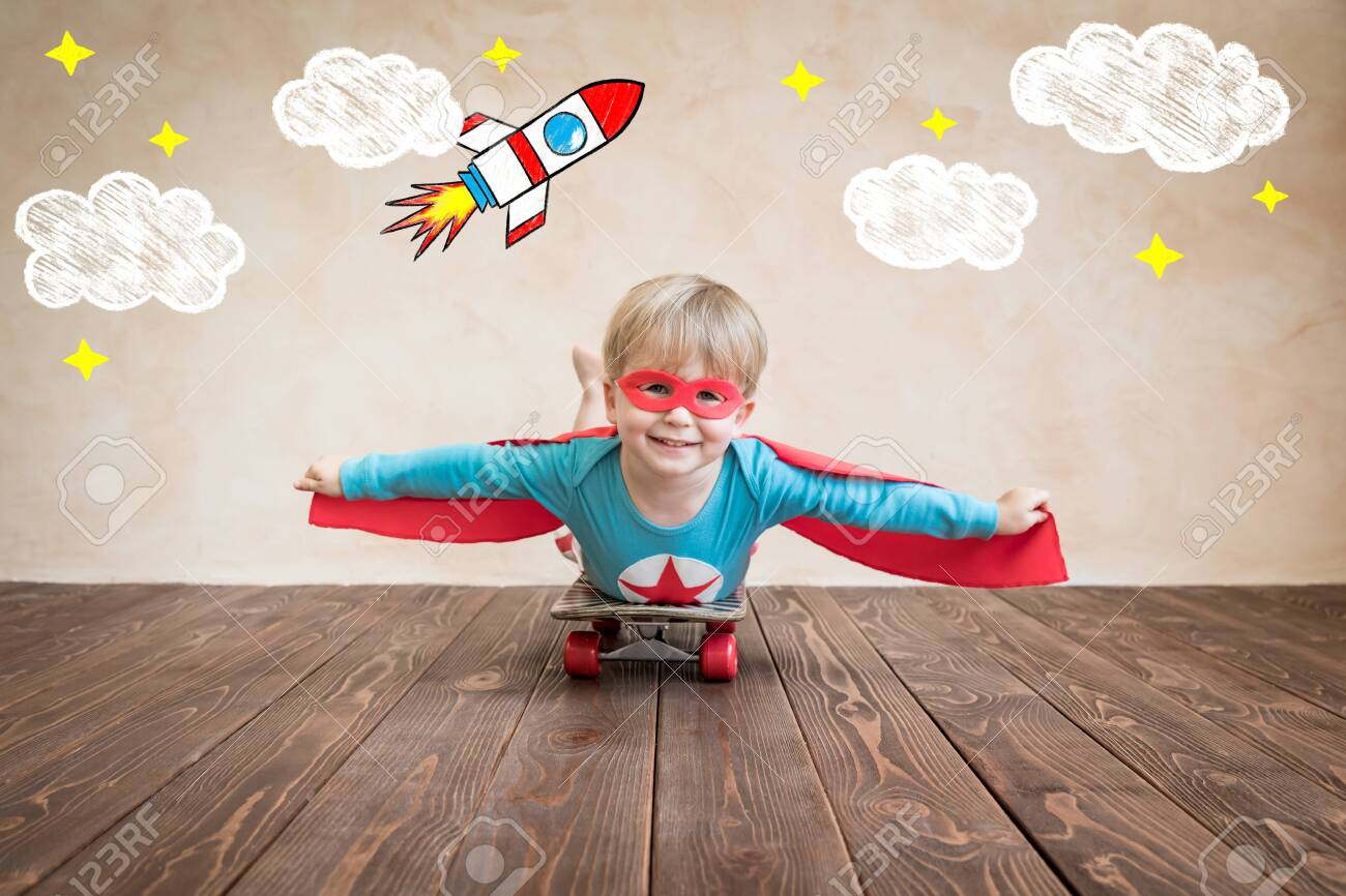 Portrait of super hero on the skateboard. Happy child playing at home. Superhero kid having fun. Success, creative and start up concept - 141832662